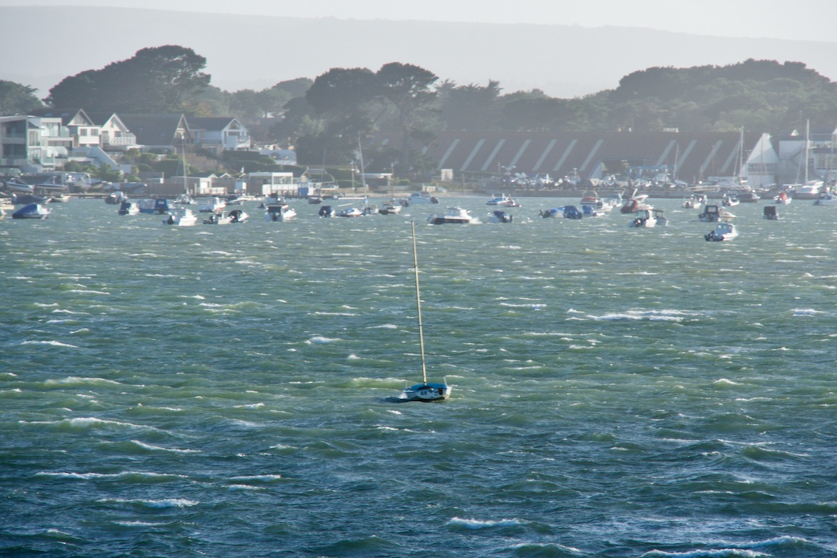 A Solitary Sailboat on Stormy Waters in Poole Harbour, Dorset