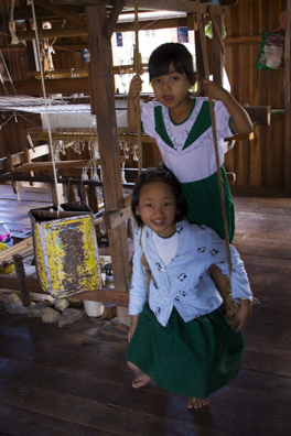 Children playing amongst the weaving looms in  Inphaw Khone Village on Lake Inle