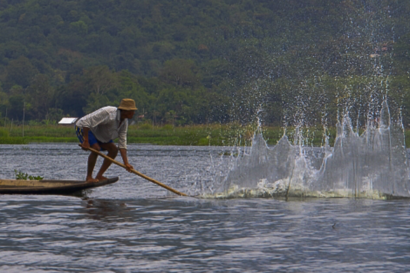 Fisherman whack the water to attract the fish on Lake Inle in Myanmar