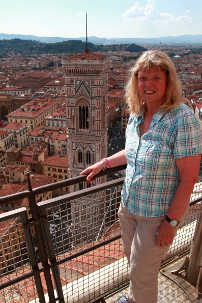 Valery standing outside the cupola of the cathedral in Florence with Giotto's tower in the background